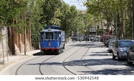 Historical blue tram carrying passengers uphill, Barcelona, Catalonia, Spain, July 2016