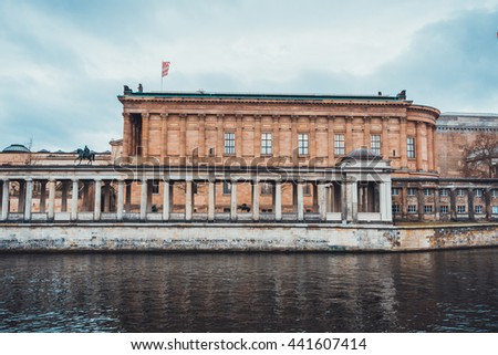 Historical Buildings, Museums and Colonnade Alongside Spree River on Museum Island on Overcast Day with Rain Clouds in Berlin, Germany - stock photo