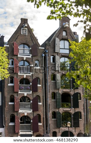Historical buildings of Amsterdam where natural green areas are protected create a nice view. Windows in the building and its construction are made of authentic stones. A colorful sunny day in summer.
