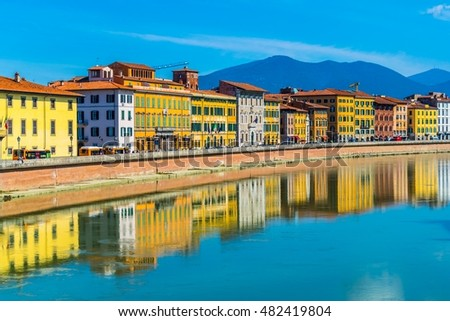 Historical buildings stretched alongside river Arno in the historical center of the italian city Pisa.