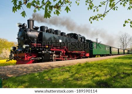 Historical German steam train passes through the fields  - stock photo