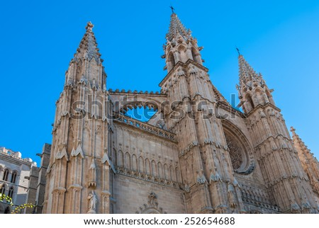 Historical Gothic Church La Seu Cathedral of Santa Maria of Palma in Majorca Front facade of a historical cathedral with a round rose window and Gothic spires, low angle view looking up - stock photo