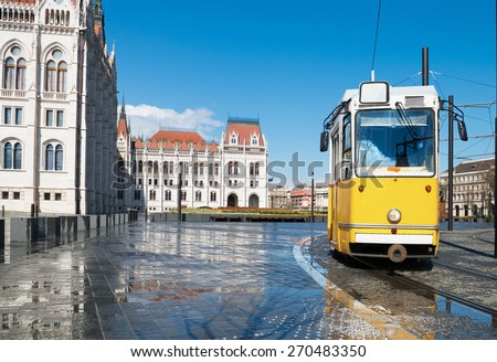 Historical tram passing by Parliament Building in Budapest, Hungary. Focus on the foreground including tram. - stock photo