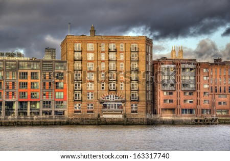 Historical warehouse converted into luxury apartments on the Thames in London, UK - stock photo