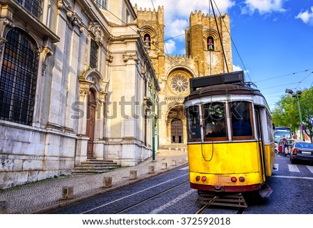 Historical yellow tram in front of the Lisbon cathedral, Alfama, Lisbon, Portugal - stock photo