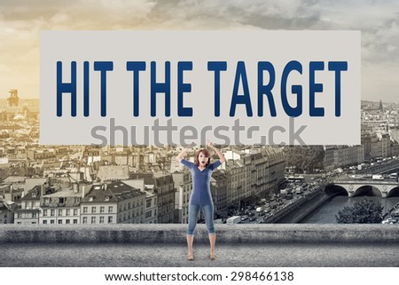 Hit the target, words on blank board hold by a young girl in the outdoor. - stock photo