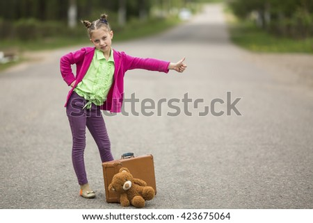 Hitch-hiking little funny girl on the road with a suitcase and a Teddy bear. - stock photo