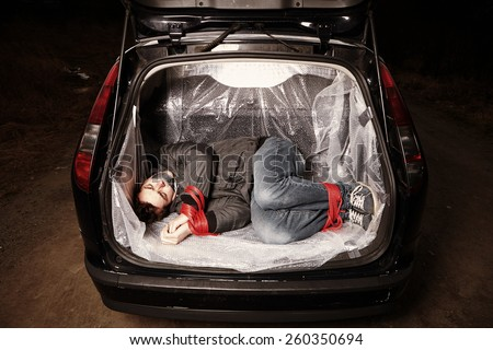 Hitch-hiking man kidnapped and bonded in car boot on local European route - stock photo