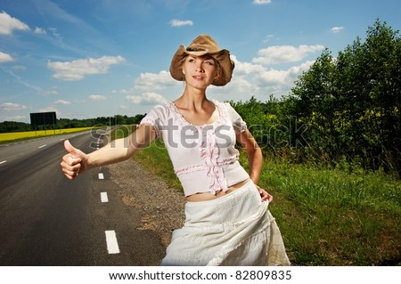 Hitchhiker girl in cowboy hat. - stock photo