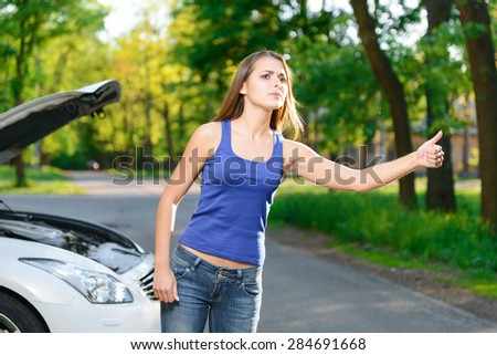 Hitchhiking. Attractive young lady standing on background of broken car with opened bonnet and trying to catch automobile - stock photo