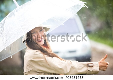 Hitchhiking girl on a road on a sunny rainy day. soft backlit, focus on face - stock photo