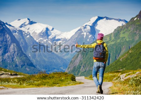 Hitchhiking tourism concept. Travel hitchhiker woman walking on road during holiday travel - stock photo