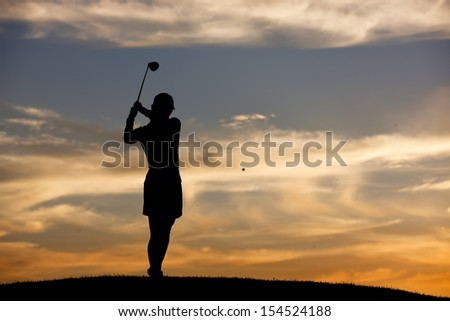 Hitting golf ball at sunset. - stock photo