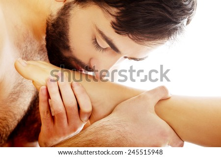 Hndsome man kissing woman's foot with desire - stock photo