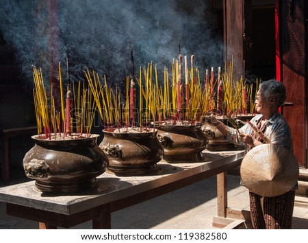 HO CHI MINH CITY - FEBRUARY 10: An unidentified woman prays in a temple during Tet on February 10, 2007 in Ho Chi Minh City, Vietnam.Tet (Vietnamese New Year) is the most important holiday in Vietnam. - stock photo