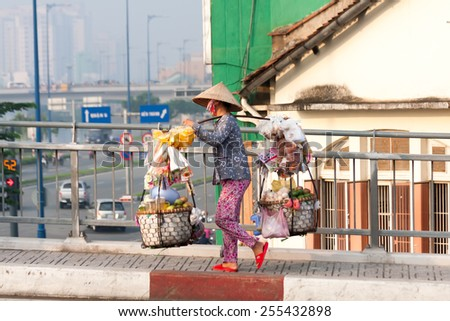 Ho Chi Minh City-Nov 1st: Street vendor on her way back across the river from the market. Vendors can be found all over the city. - stock photo
