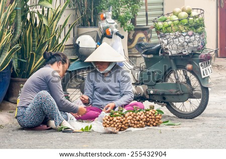 Ho Chi Minh City-Nov 1st 2013: Women sorting longan fruit . Street vendors can be found all over the city - stock photo