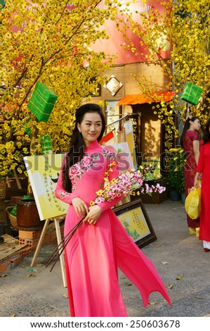 HO CHI MINH CITY, VIET NAM- FEB 7: Atmosphere of springtime with colorful scene on Saigon street, Vietnamese woman in ao dai, posing beside flower to take photo on Tet holiday, Vietnam, Feb 7, 2015