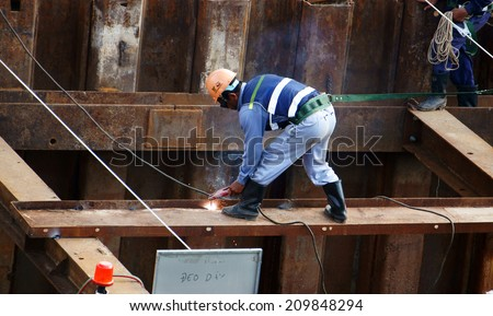 HO CHI MINH CITY, VIETNAM- AUG 9 : Construction worker working on bridge site at Sai Gon river, this project belong metro plan from Ben Thanh, man welding steel bar on Viet Nam,  August 9, 2014