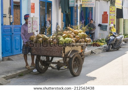 HO CHI MINH CITY, VIETNAM  - AUG 23: Unidentified local coconut seller on the street of Ho Chi Minh City  on Aug 23, 2014. - stock photo