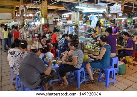 HO CHI MINH CITY, VIETNAM - AUGUST 6th: Visitors have lunch inside the Ben Thanh Market on August 6, 2013 in Ho Chi Minh City. Ben Thanh Market is a large marketplace of Ho Chi Minh City. - stock photo