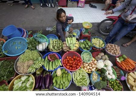 HO CHI MINH CITY, VIETNAM- CIRCA JUNE 2010: Street Vendor in Ho Chi Minh City, Vietnam selling vegetables on the sidewalk (Ho Chi Minh City, Vietnam - CIRCA June, 2010) - stock photo