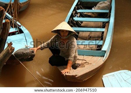 Ho Chi Minh City, Vietnam - Feb 19, 2009: Vietnamese woman floating on a boat on the yellow waters of the Mekong River - stock photo