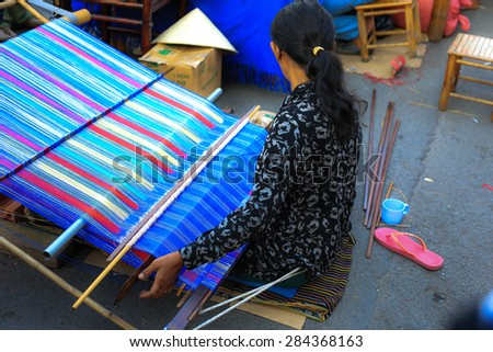 Ho Chi Minh city, Vietnam - February 20, 2015: a woman of ethnic minorities are manipulating machine brocade weaving his primitive in a New Year's festival in Ho Chi Minh City