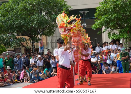 Ho Chi Minh City, Vietnam - February 18, 2017 :  people watching dragon and lion dance show in a street festival