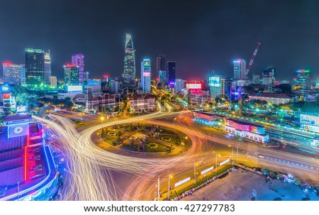 Ho Chi Minh City, Vietnam - July 23rd, 2015: Impressive beauty, colorful traffic when city lights up, trail vehicle in crowded Quach Thi Trang roundabout, Ho Chi Minh city, Vietnam