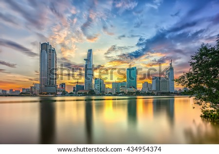 Ho Chi Minh City, Vietnam - June 9th, 2016: Riverside City sunset clouds in sky at end of day brighter coal sparkling skyscrapers along beautiful river in Ho Chi Minh City, Vietnam