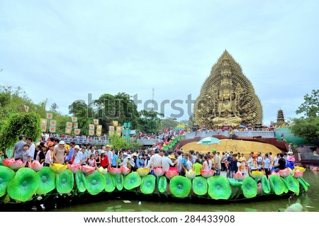 HO CHI MINH CITY, VIETNAM - MARCH 31, 2012: Crowd of Buddhists are offering incense to Buddha with thousand hands and thousand eyes in the Suoi Tien park in Saigon - stock photo