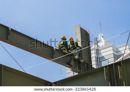 HO CHI MINH CITY, VIETNAM - SEP 18: Builder workers in safety protective equipment assemble metal construction frame with spanner tools in Ho chi Minh City on Sep 18, 2014 - stock photo
