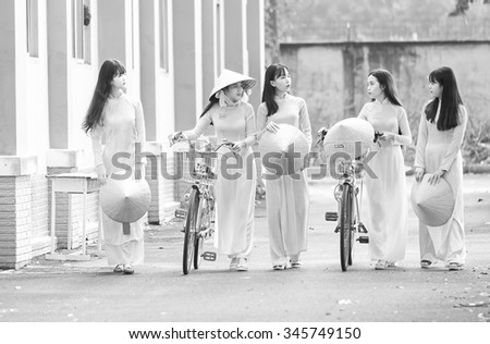 Ho Chi Minh City, Vietnam - September 13rd, 2015: Group student girls chatting on way to school with long dress, conical hats and bike pretty creating in the morning Ho Chi Minh city, Vietnam