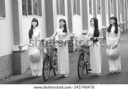 Ho Chi Minh City, Vietnam - September 13rd, 2015: Group teenager girls in long dress is leading bicycle to go to school with smiling face in morning Ho Chi Minh City, Vietnam