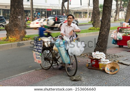 Ho Chi Minh City, Vietnam-29th Oct 2013: A street vendor peddles his wares. Street vendors can be found all over the city. - stock photo