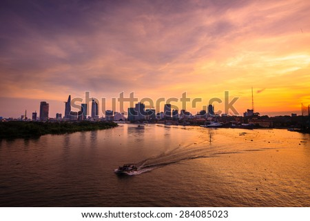 Ho Chi Minh's Panorama view over the Saigon River. Dramatic lighting spectacular sunset is highlighted by a canoe surfing on the water at a faster rate