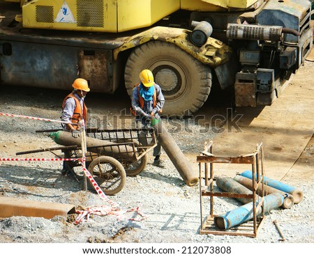 HO CHI MINH, VIETNAM- AUG 9 : Vietnamese construction worker working on site, this project belong metro plan from Ben Thanh, two man transport gas tank, energy source, Viet Nam,  August 9, 2014 - stock photo