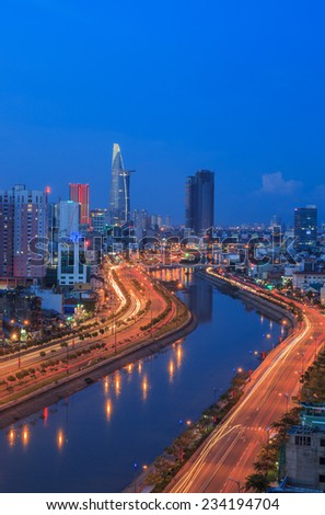 HO CHI MINH, VIETNAM - AUGUST 31, 2013 : Arial view at  Vo Van Kiet Highway in Ho Chi Minh city with the bridge cross the canal, buildings and traffic light trail at night - stock photo