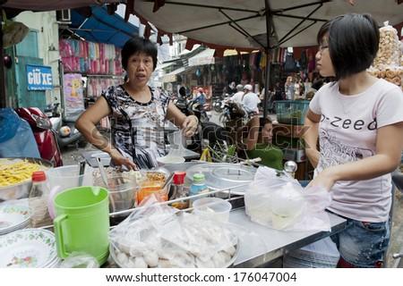 HO CHI MINH, VIETNAM - DECEMBER 27 : Unidentified street food vendor in the street in Saigon (Ho Chi Minh city), Vietnam on December 27, 2011 - stock photo