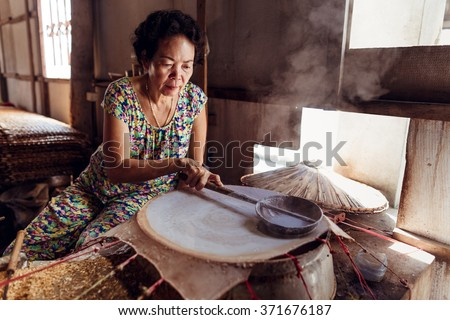 HO CHI MINH, VIETNAM - JAN 15, 2016: The woman cooking the rice pancake in the village near the Mekong river in Hochiminh (Saigon). Saigon is the largest city in Vietnam