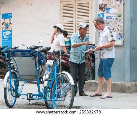 HO CHI MINH, VIETNAM - JULY 7, 2014: An unidentified Caucasian tourist pays to a cyclo driver in the downtown. Many cyclo drivers in District 1 are eager to provide their services as tour guides. - stock photo