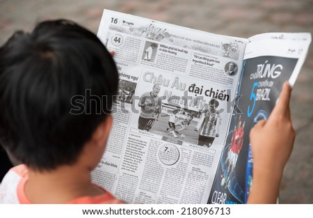 HO CHI MINH, VIETNAM - JULY 7, 2014: An unidentified teenager reads about the Football World Cup in a newspaper. Germany won the tournament  by defeating Argentina 1 - 0 in the final.