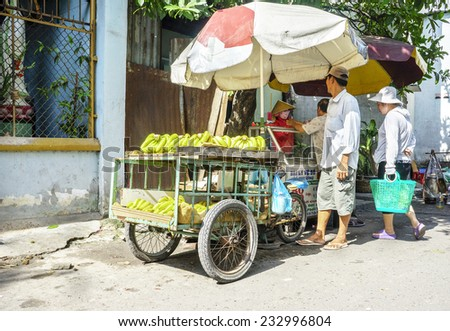 HO CHI MINH, VIETNAM - JULY 13: Man selling Tropical fruits at market on July 13, 2013 in Ho Chi Minh, Vietnam. Hochiminh city is the biggest city and economic . - stock photo