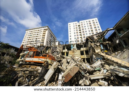 HO CHI MINH, VIETNAM - JULY 13: track-type loader excavator machine doing demolition work at old building on July 13, 2013 in Ho Chi Minh, Vietnam.Hochiminh city is the most developed city of Vietnam - stock photo