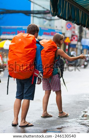 HO CHI MINH, VIETNAM - JULY 8, 2014: Two unidentified Caucasian tourists with big backpacks ask for a menu at a street cafe in Bui Vien Street. There are a lot of such cafes in the Pham Ngu Lao area.  - stock photo