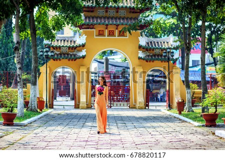 "HO CHI MINH, VIETNAM - MAY 10, 2016: Vietnamese girl traditional dress, "" Ao dai "" is famous traditional costume for woman in Vietnam at pagoda"
