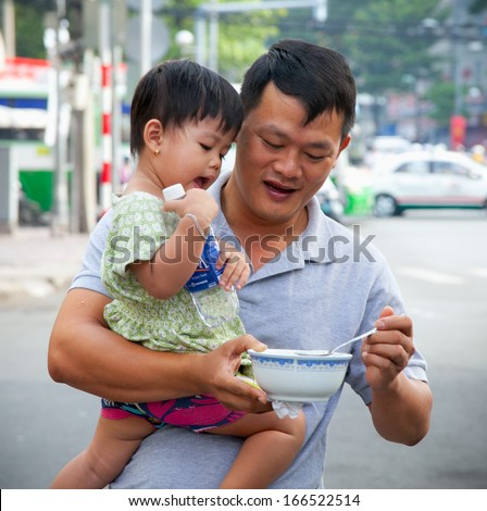 HO CHI MINH,VIETNAM-NOVEMBER 17,2013:Father feeding daughter on the street of Ho Chi Minh,Vietnam on November 17, 2013.According to UNICEF, gross national income (GNI) for Vietnam in 2013 is USD$1,4. - stock photo