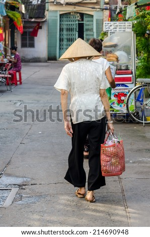 HO CHI MINH, VIETNAM - SEP 02: Unidentied old woman going to the market on September 02, 2014 in Ho Chi Minh city, Vietnam. - stock photo