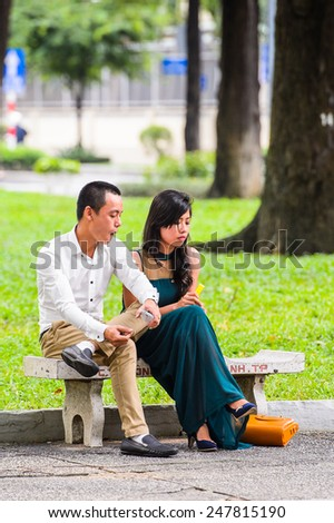 HO CHI MINH, VIETNAM - SEP 20, 2014: Unidentified Vietnamese couple on a bench in the street. 90% of Vietnamese people belong to the Viet ethnic group